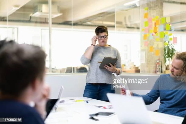 rédacteur féminin utilisant la tablette numérique dans la salle de conseil - salle de presse photos et images de collection