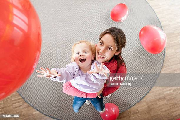 Female educator and little girl playing with red balloons in kindergarten