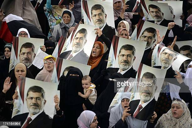Female Egyptian supporters of the Muslim Brotherhood hold up portraits of Egypt's ousted president Mohamed Morsi during a rally in Cairo on July 21...