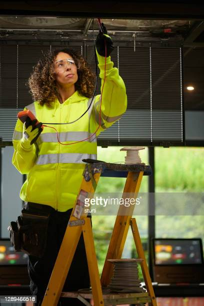 female electrician installing aircon - females stock pictures, royalty-free photos & images