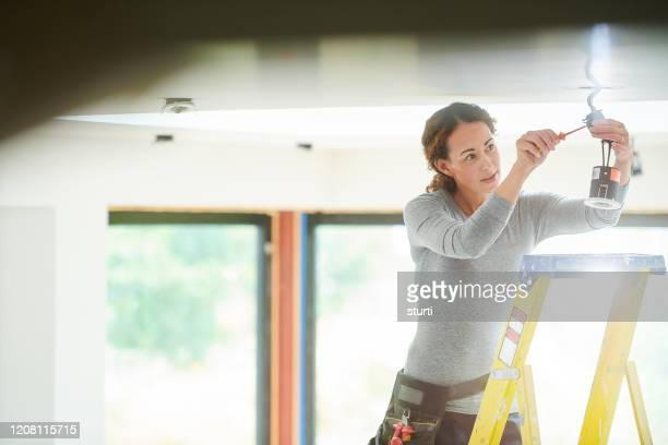 female electrician installing downlights - service stock pictures, royalty-free photos & images
