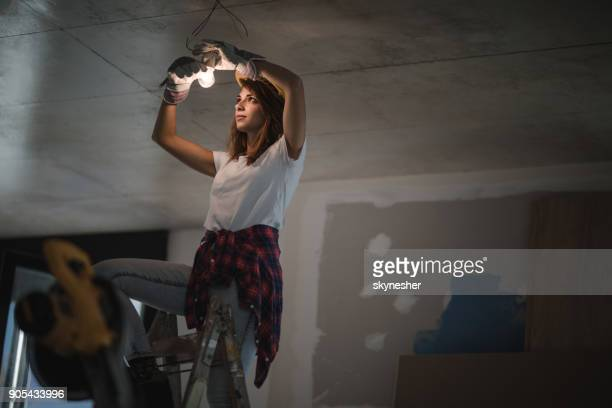 female electrician tightening light bulb during home renovation process. - ceiling stock pictures, royalty-free photos & images