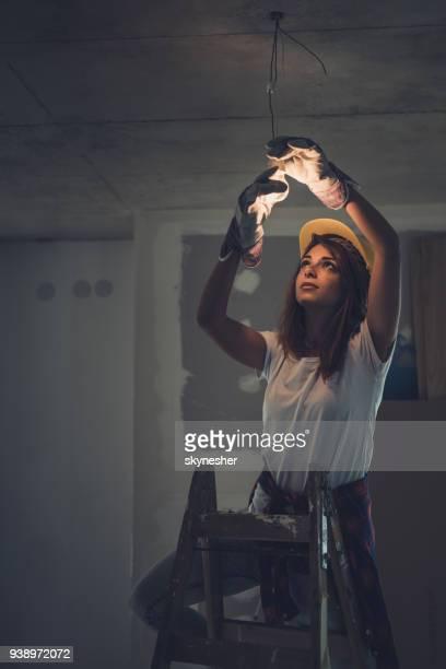 Weibliche Elektriker Glühbirne bei Renovierungs anziehen.