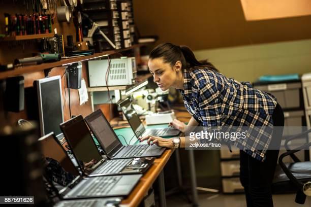 Female electronic engineer examining computer