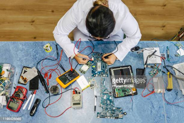 female electronic engineer testing computer motherboard in laboratory - oscilloscope stock pictures, royalty-free photos & images