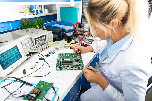 Female electronic engineer testing computer motherboard in laboratory 843765236