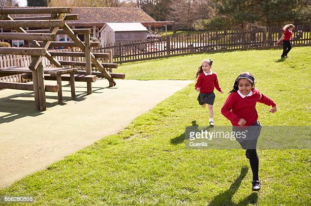 female elementary school pupils playing tag at breaktime - kids playing tag ストックフォトと画像