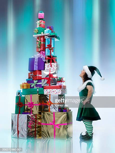 Female 'Elf' standing by large pile of presents (digital composite)
