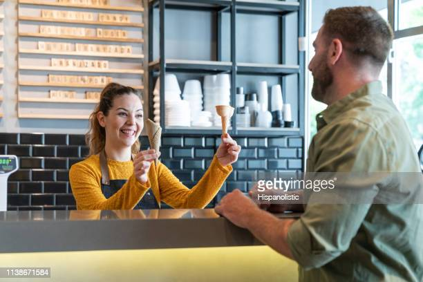 female employee at an ice cream parlor showing different ice cream cones to male customer - ice cream parlour stock pictures, royalty-free photos & images