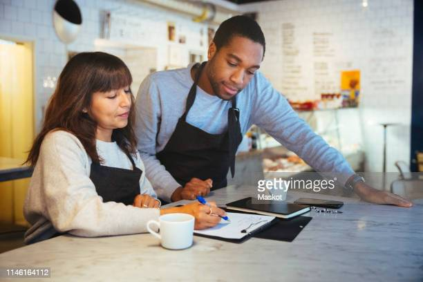 Female employee discussing over clipboard with male coworker at table in cafe