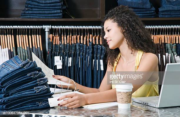 Female employee in clothing boutique working at desk