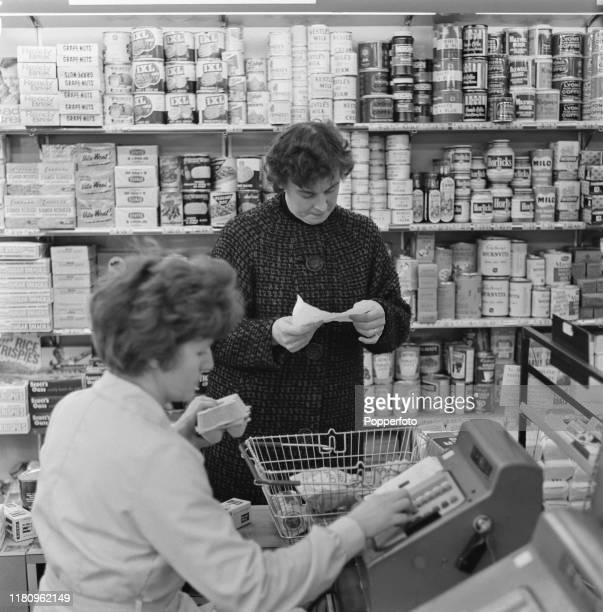 A female employee operates a cash register to ring up a customer's shopping at the checkout till of a supermarket in England in December 1966
