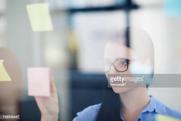 Female employee placing sticky notes on glass