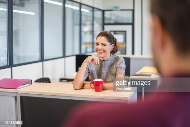 female employee sitting at desk, talking to colleague - employee appreciation stock pictures, royalty-free photos & images