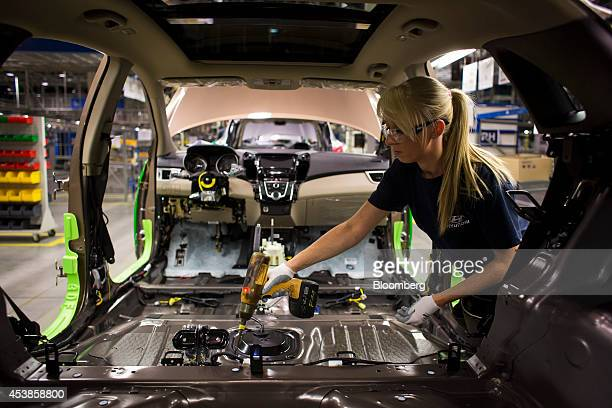 Female employee uses a cordless drill as she works on the interior assembly of an automobile on the production line at Hyundai Motor Co.'s plant in...