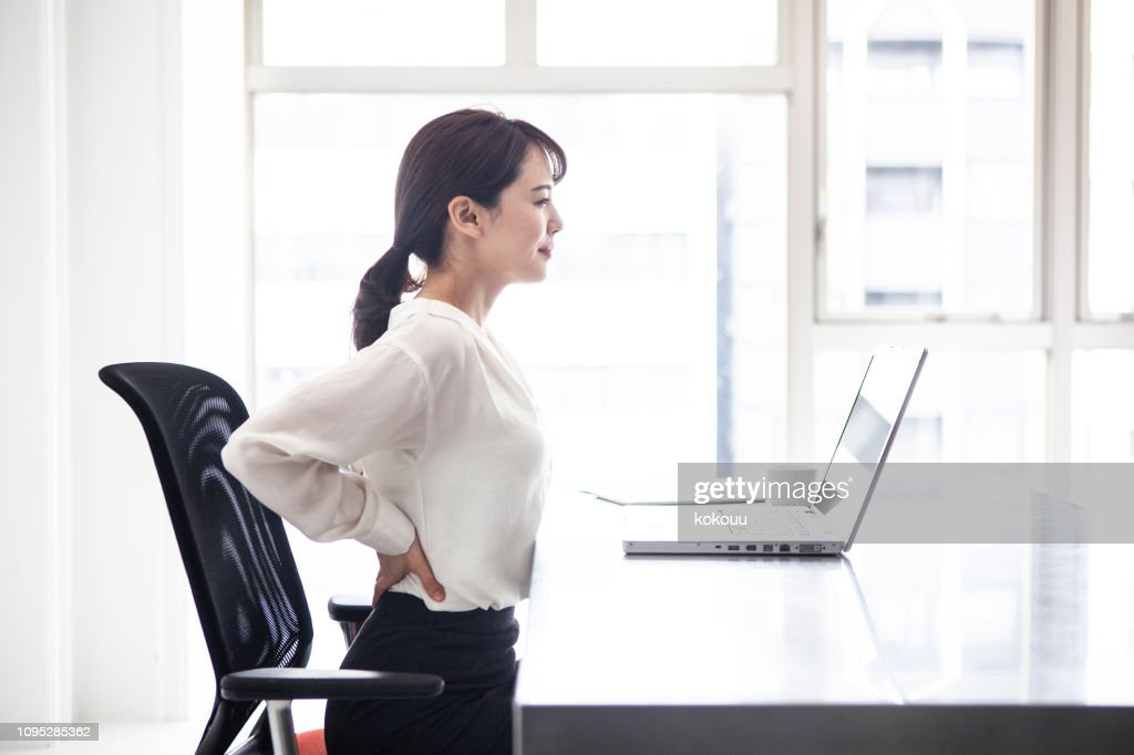 Female employees are suffering from low back pain : Stock Photo