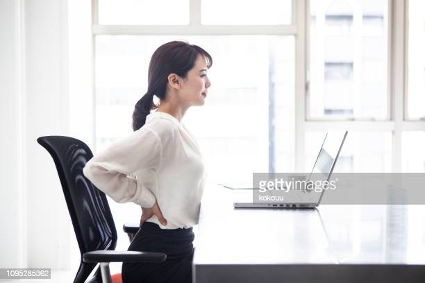 female employees are suffering from low back pain - lower back stock pictures, royalty-free photos & images