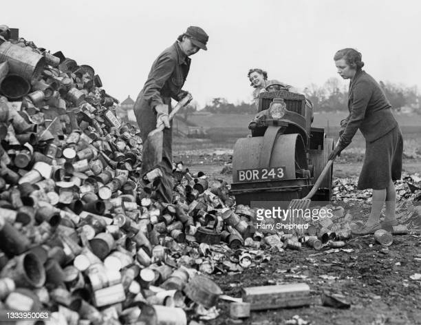 Female employees from the Ministry of Works use a Wallis & Steevens 'Advance' brand diesel engined road roller to crush and flatten scrap tin cans to...