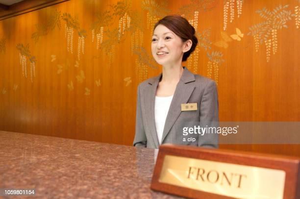 フロントに立つ女性従業員 - ホテルマン ストックフォトと画像