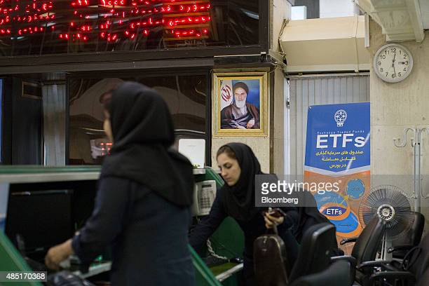 Female employees work near a portrait of Ruhollah Khomeini founder of the Islamic republic of Iran at the Tehran Stock Exchange in Tehran Iran on...