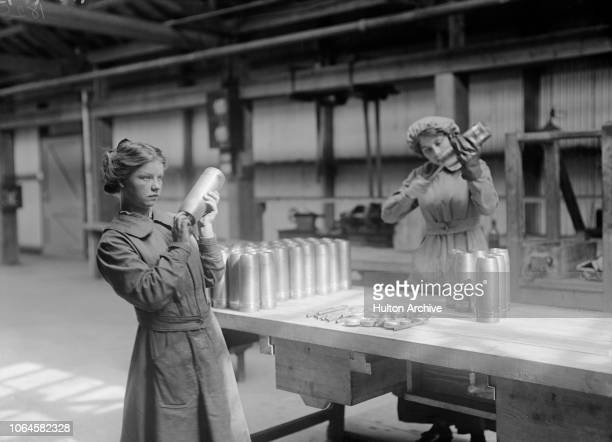 Female employees working on shell casings at a Vickers Ltd munitions factory, UK, circa 1915.