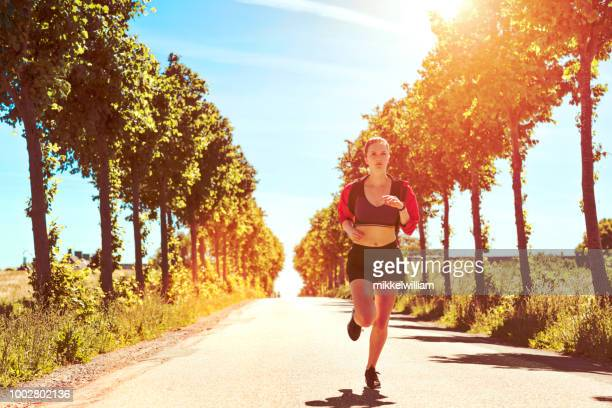 Female endurance runner makes her way forward on lonely road in the country side
