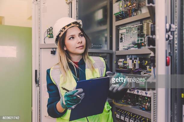 female energy station electrician engineer working at energy control room - fuse stock photos and pictures