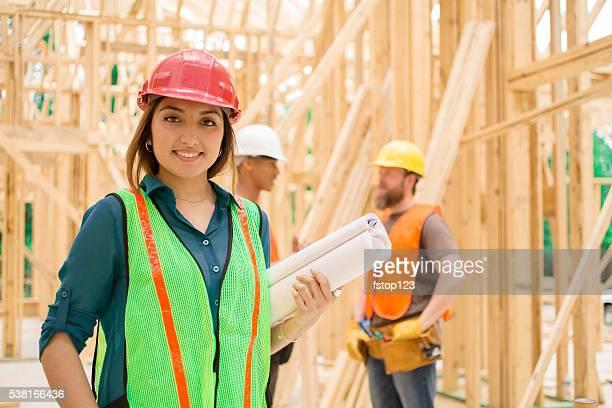 Female engineeer.  Construction job site. Framed building.