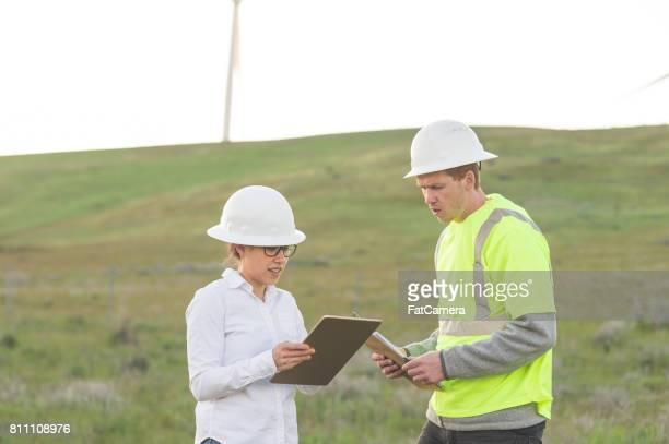 Kvinnlig ingenjör och hennes manliga kollega göra en inspektion på plats vid en vindkraftpark