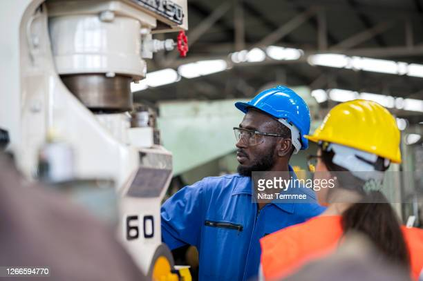 female engineer and operator technical testing program a cnc milling machine in a foundry industry. - black jumpsuit stock pictures, royalty-free photos & images