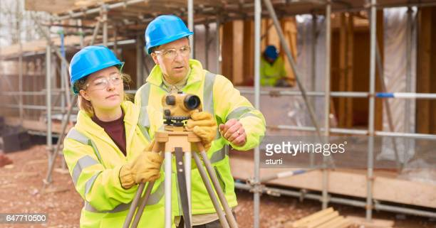 female engineer apprentice with supervisor on building site.