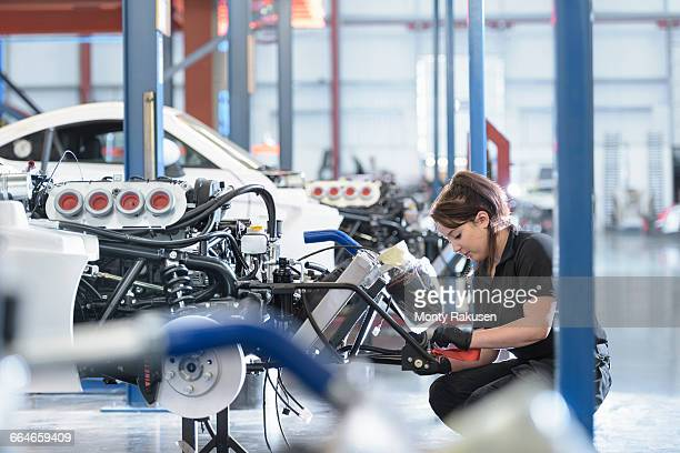 Female engineer assembles car in racing car factory