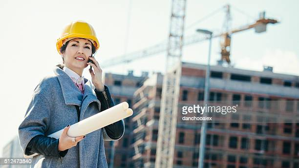 Female engineer at construction site talking on the phone
