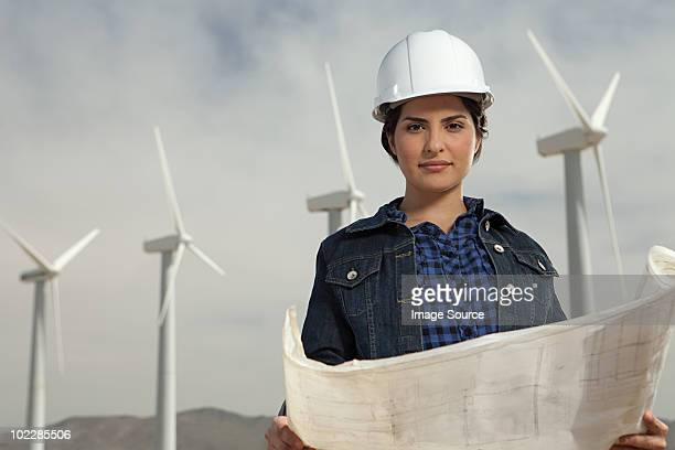 Female engineer at wind farm with plans