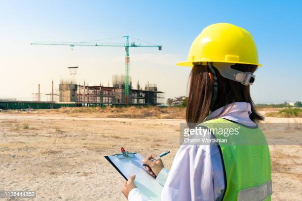 female engineer. construction job site. framed building. - real estate developer stock pictures, royalty-free photos & images