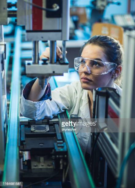 female engineer examining machine part on a production line. - stem assunto imagens e fotografias de stock