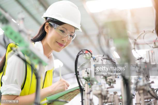 female engineer examining machine part on a production line. - technician stock pictures, royalty-free photos & images