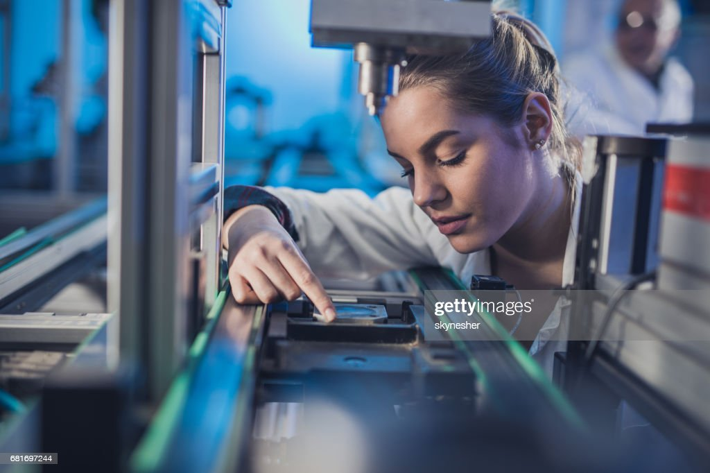 Female engineer examining machine part on a production line. : Stock Photo