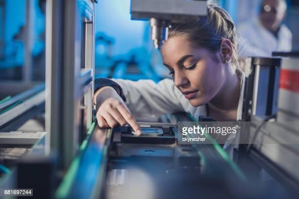 Ingenieurin Maschinenteil auf einer Produktionslinie zu prüfen.