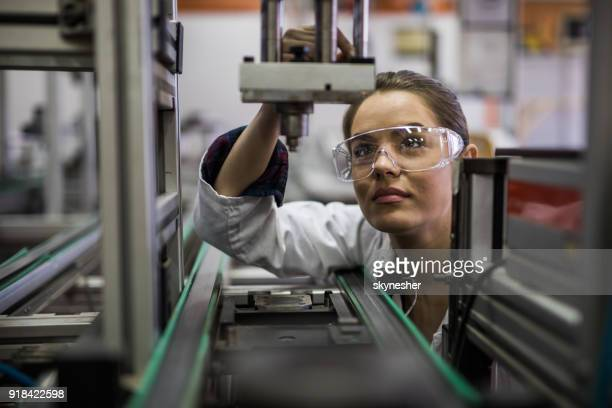 Female engineer examining machine part on a production line.