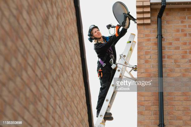 female engineer fixing an aerial - high up stock pictures, royalty-free photos & images