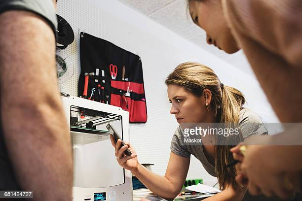 Female engineer holding smart phone and looking at 3D printer with colleagues