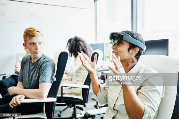 female engineer in discussion with coworker while testing program on augmented reality headset in computer lab - digital native stock pictures, royalty-free photos & images