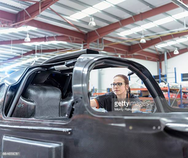 Female engineer inspecting carbon fibre body in racing car factory