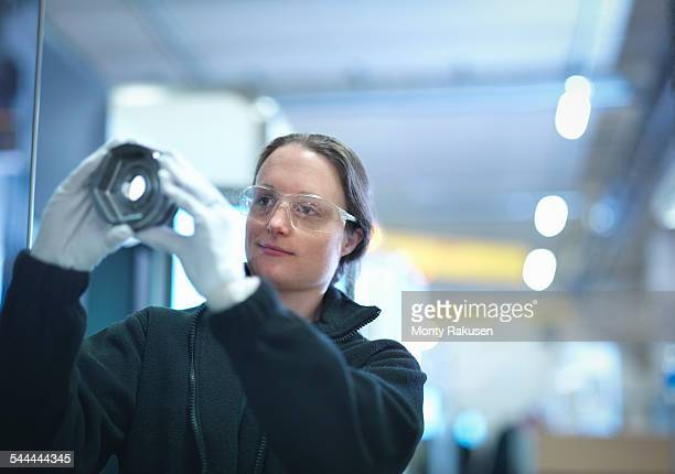 Female engineer inspecting part in factory