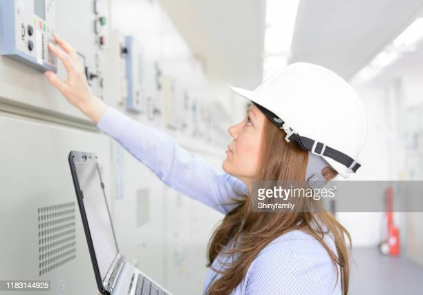 female engineer is checking equipment in power substation - energy efficient stock pictures, royalty-free photos & images