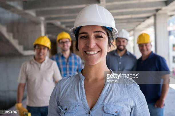 Female engineer leading a group of construction workers