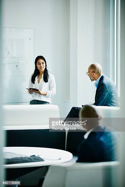 Female engineer leading team meeting in office