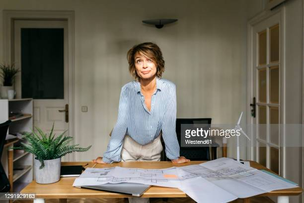 female engineer leaning on desk while standing in office - leaning stock pictures, royalty-free photos & images