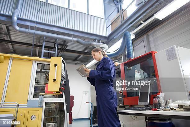 female engineer monitoring factory machinery using digital tablet - sigrid gombert stock-fotos und bilder